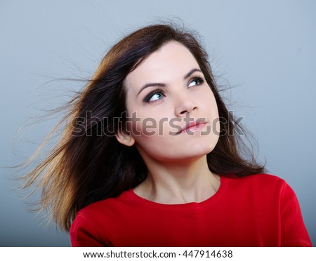 Happy girl in a red shirt with hair flying on a gray background
