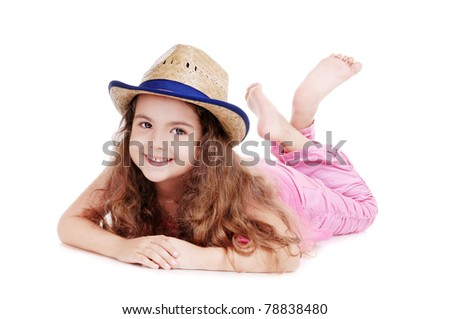 Happy girl in a straw hat laying on the floor