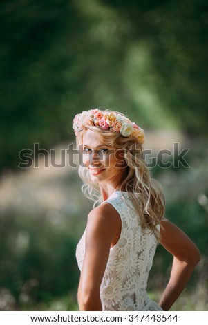 happy girl in a white dress with a handmade wreath of flowers on the head in the green forest - stock photo