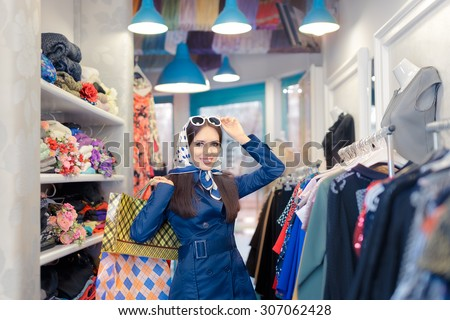 Happy Girl in Blue Trench Coat and Sunglasses Shopping - Retro young woman in a raincoat in a clothing store