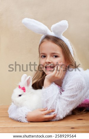 Happy girl in bunny costume holding her white rabbit - laying on wooden floor - stock photo