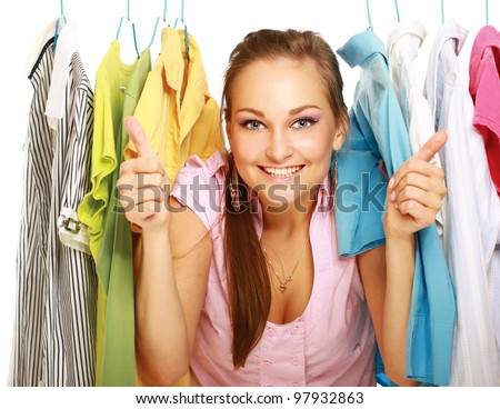 Happy girl in clothing store showing thumbs up isolated