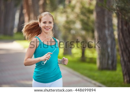 happy girl in for sports and fitness jogging  in the summer in the park