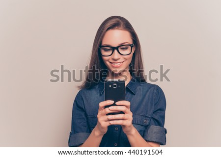 Happy girl in glasses typing sms on gray background - stock photo