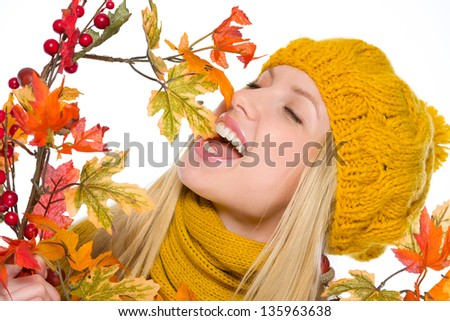 Happy girl in hat and scarf playing with autumn bouquet