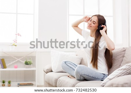 Happy girl in headphones at home. Sitting comfortably on beige sofa listening to music while. Copy space