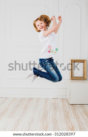 Happy girl in jeans jumping in light room