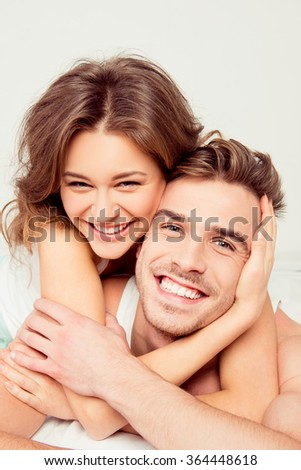 Happy girl in love at home embracing boyfriend - stock photo