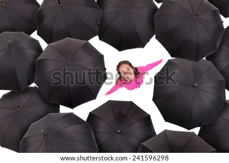 Happy girl in pink amongst black umbrellas - stock photo