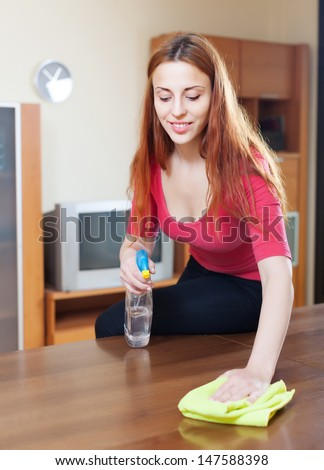 Happy  girl in red cleaning table with  furniture polish at home  - stock photo