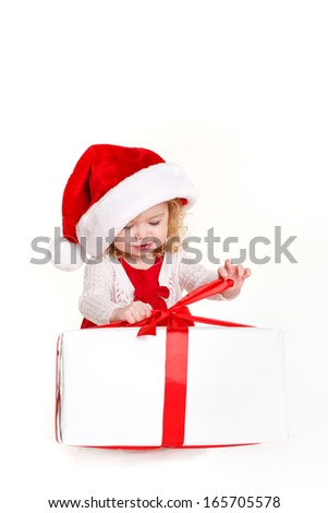 Happy girl in Santa hat unwrapping ribbon of christmas present isolated on white background - stock photo