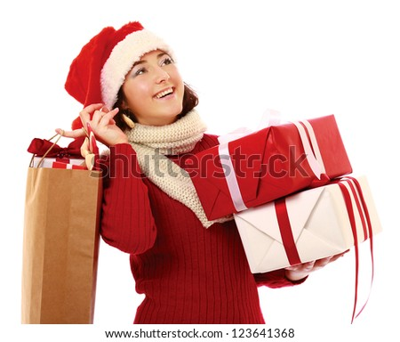 Happy girl in santa hat with bag full of gifts isolated on white background