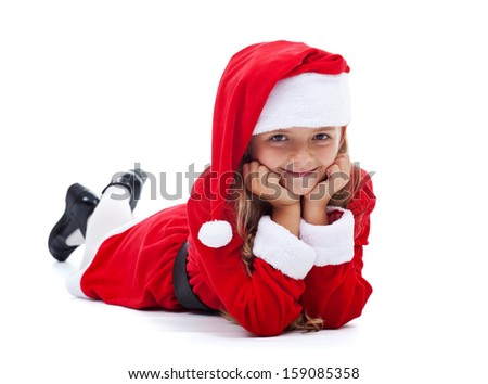 Happy girl in Santa outfit smiling laying on the floor- isolated