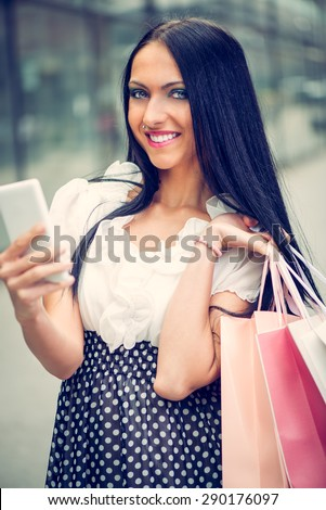 Happy girl in shopping walking out of shopping mall with bags and smart phone in their hands. Looking at camera