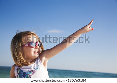 Happy girl in sunglasses pointing at sun on the beach - stock photo