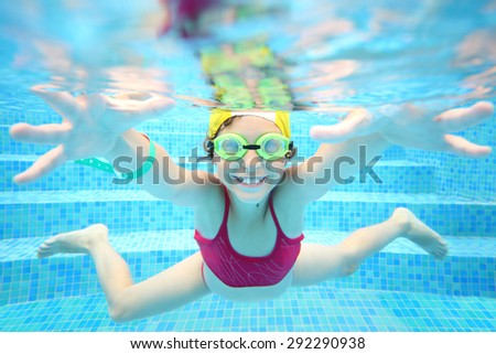 Happy girl in swimming glasses under water in the pool - stock photo