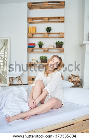 Happy girl in the apartment on the bed - stock photo