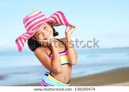 Happy girl in the beach wearing a hat and colorful swimming suit.