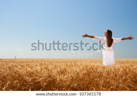 Happy girl in white dress on wheat field - stock photo