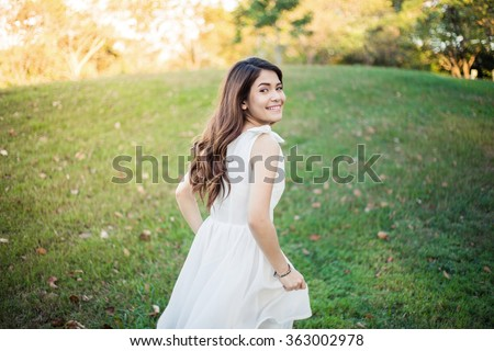 Happy girl in white dress running on grass field in the garden - stock photo