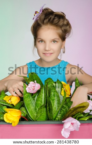 happy girl is caring for flowers on a colored background - stock photo