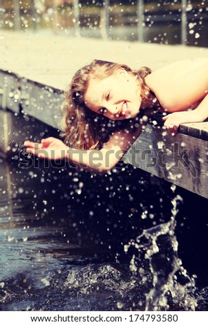 Happy girl is laughing in sunny day. Young woman is lying on the bridge with head directed down and splashing water. - stock photo