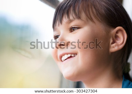 Happy girl is looking through window while sitting in train, closeup shoot - stock photo