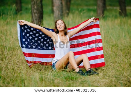 Happy girl is sitting on the grass with the American flag