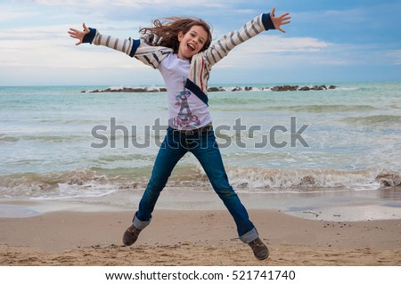 Happy girl jumping along the sea