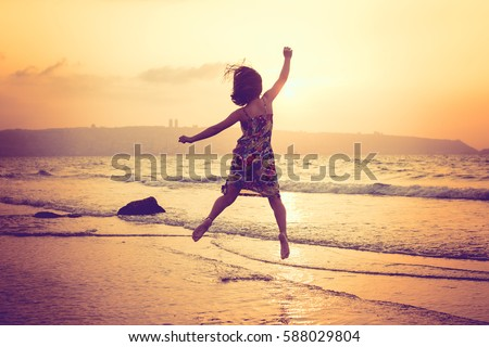 happy girl jumping at the beach, sunset shot