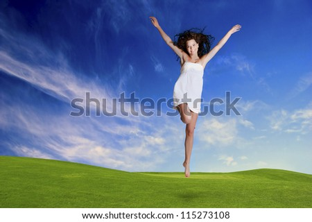 Happy girl jumping in a beautiful green meadow - stock photo