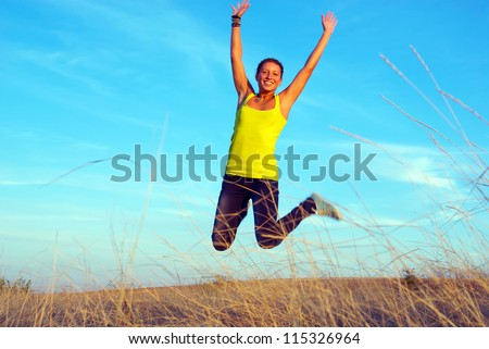 Happy girl jumping in the air on a background sky