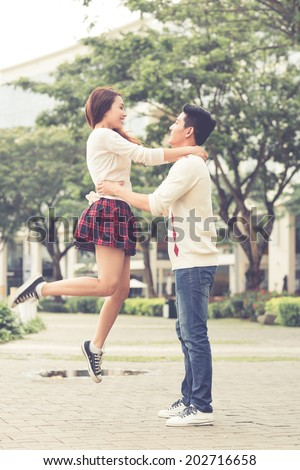 Happy girl jumping into arms of her boyfriend - stock photo