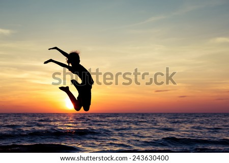 Happy girl jumping on the beach at the sunset time.