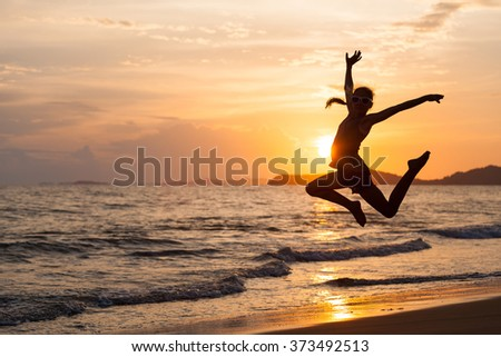 Happy girl jumping on the beach at the sunset time