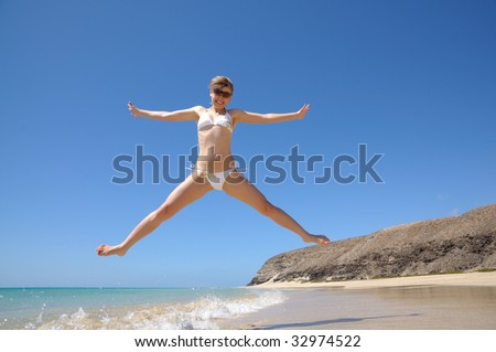 Happy girl jumping on the beach, Fuerteventura, Canary Islands Spain - stock photo