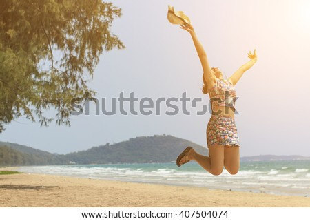 Happy girl jumping on the beach with sunlight -motion  blur   - stock photo