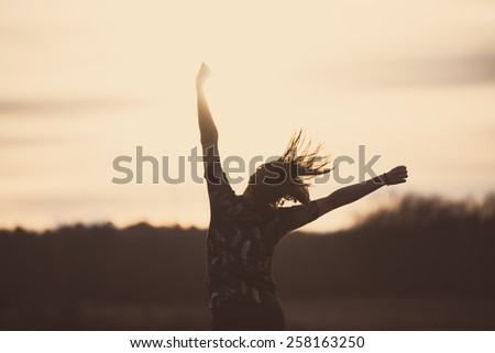 Happy girl jumping on the dawn time.Happy woman jumps to the sky in the yellow meadow at the sunset.Happy woman jumping against sunset. Freedom concept. Enjoyment.