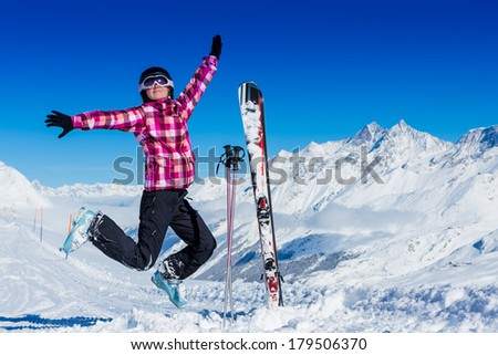 Happy girl jumping over blue sky and snow background, teen outdoor winter activities, female having fun at Christmastime, woman wearing colorful clothes, freedom and success concept