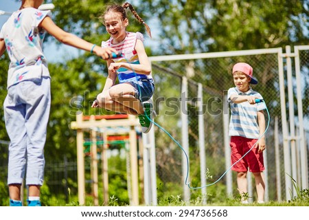 Happy girl jumping over skipping-rope held by her friends outdoors - stock photo