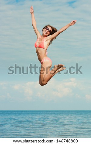Happy girl jumping over the sea.