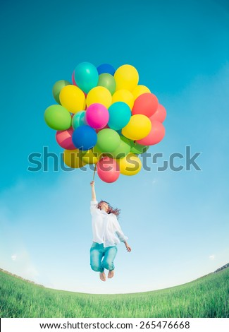 Happy girl jumping with colorful toy balloons outdoors. Young woman having fun in green spring field against blue sky background. Freedom concept - stock photo