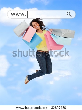 Happy girl jumping with her shopping bags under address bar on blue sky background