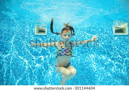 Happy girl jumps and swims in pool underwater, happy active child has fun in water, kid sport on family vacation  - stock photo