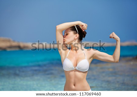happy girl kisses her body muscle - stock photo