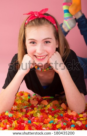 Happy girl laying in a pile of colorful candy including gummi bears, jelly beans, gumdrops and more. - stock photo