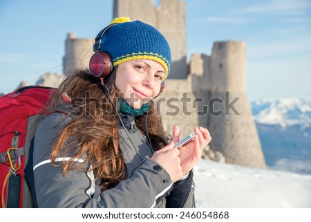 Happy girl listening to music on top of the mountain, Italy