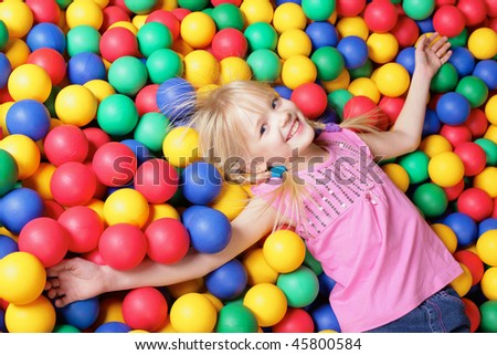 Happy girl lying on colorful balls and looking at camera