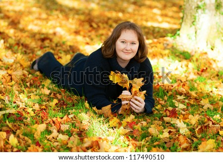 Happy girl lying on the ground in park on a fall day
