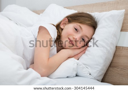 Happy Girl Lying With Pillow And Blanket In Bed - stock photo